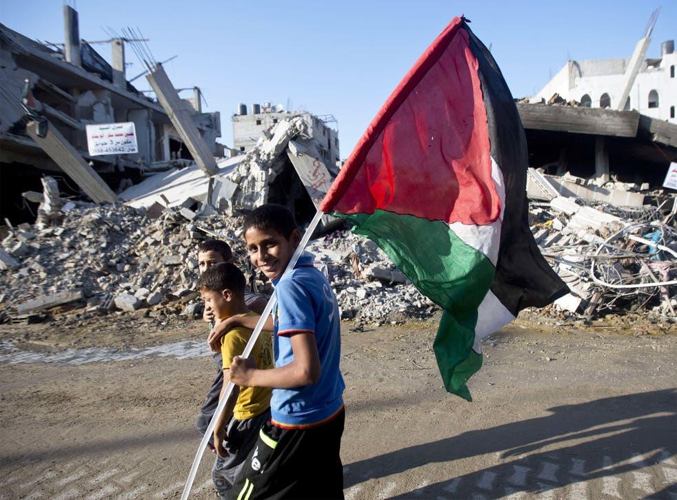 Palestinian children smile while walking through a scene of destruction