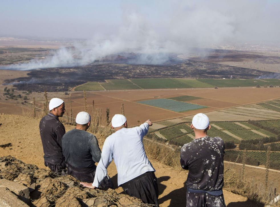 Druze men in the Golan Heights look on as smoke rises from the fighting between forces loyal to President Assad and rebels over the control of the Quneitra border crossing