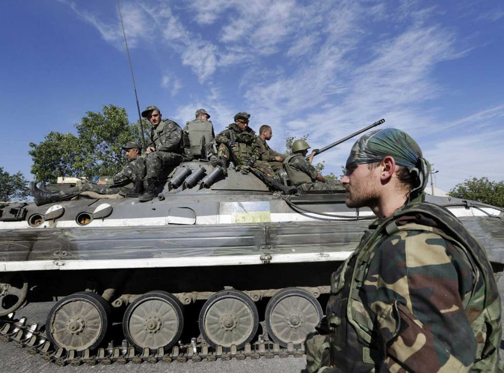 A pro-Russian rebel watches Ukrainian troops retreat from the rebel-held town of Starobesheve yesterday