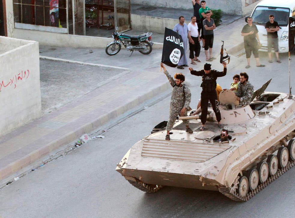 """Militant Islamist fighters take part in a military parade along the streets of northern Raqqa province June 30, 2014. Militant Islamist fighters held a parade in Syria's northern Raqqa province to celebrate their declaration of an Islamic """"caliphate"""" afte"""