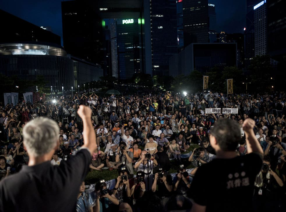 Benny Tai (R), co-founder of the Occupy Central movement, rallies with democracy activists next to the Hong Kong government complex on August 31