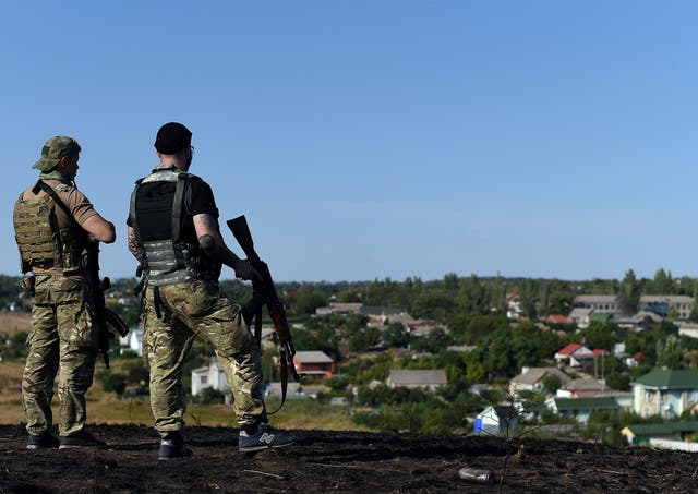 Ukrainian loyalist fighters from the Azov Battalion stand guard on a hill on the outskirts of Mariupol on August 30, 2014