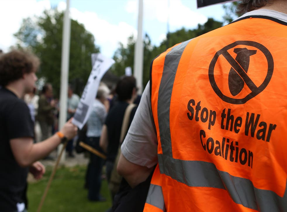 A man, wearing a 'Stop the War Coalition' jumper, marches against government plans to station surface-to-air missiles on the roof of their rented flats near London's Olympic Park.