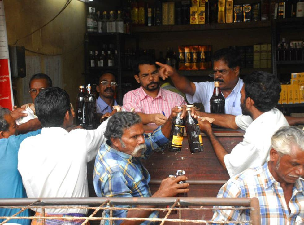 Customers buying liquor from a government shop in Kerala (Getty)