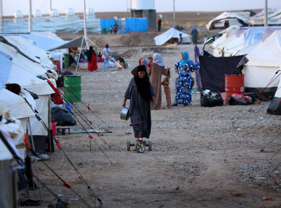 An Iraqi woman, who fled violence in the northern city of Tal Afar, walks through the Bahrka camp