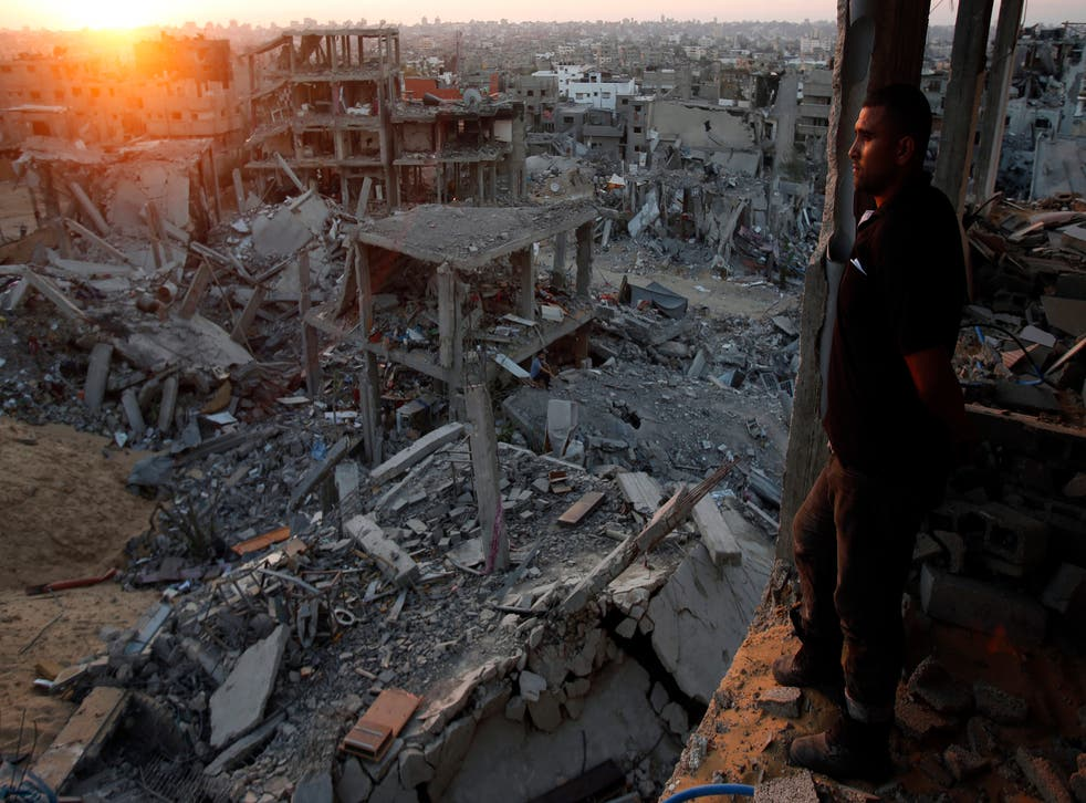 A Palestinian man looks out of his heavily damaged house at neighbouring houses in the east of Gaza City 3 September 2014
