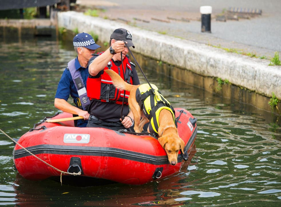 Police search the River Brent, near Hanwell, west London, today
