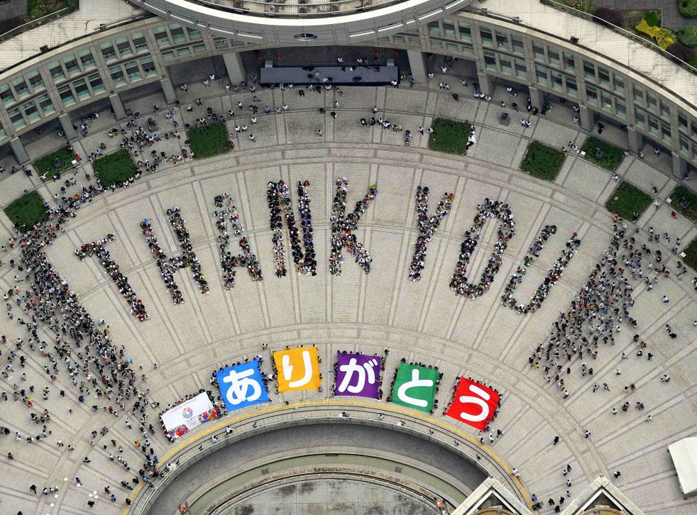 """An aerial view shows people sitting in formation to the words """"thank you"""" and displaying signs that collectively read """"Arigato"""" (Thank You) during an event celebrating Tokyo being chosen to host the 2020 Olympic Games, at Tokyo Metropolitan Government Building in Tokyo"""
