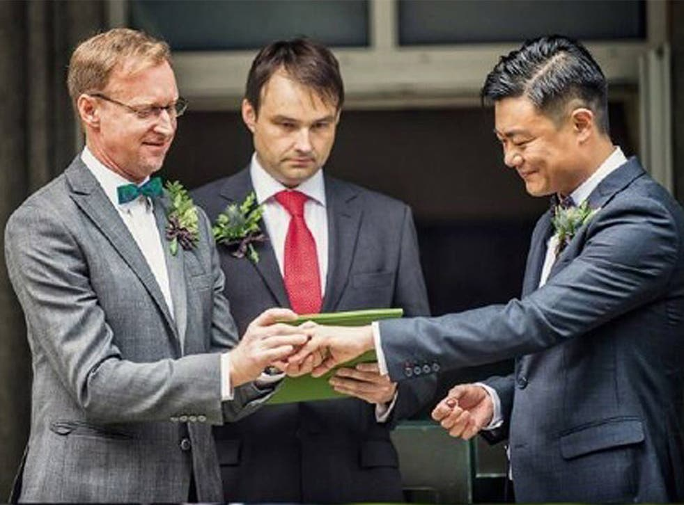 Brian Davidson and his partner Scott Chang exchanging the rings during their wedding ceremony at the British ambassador's residence in Beijing