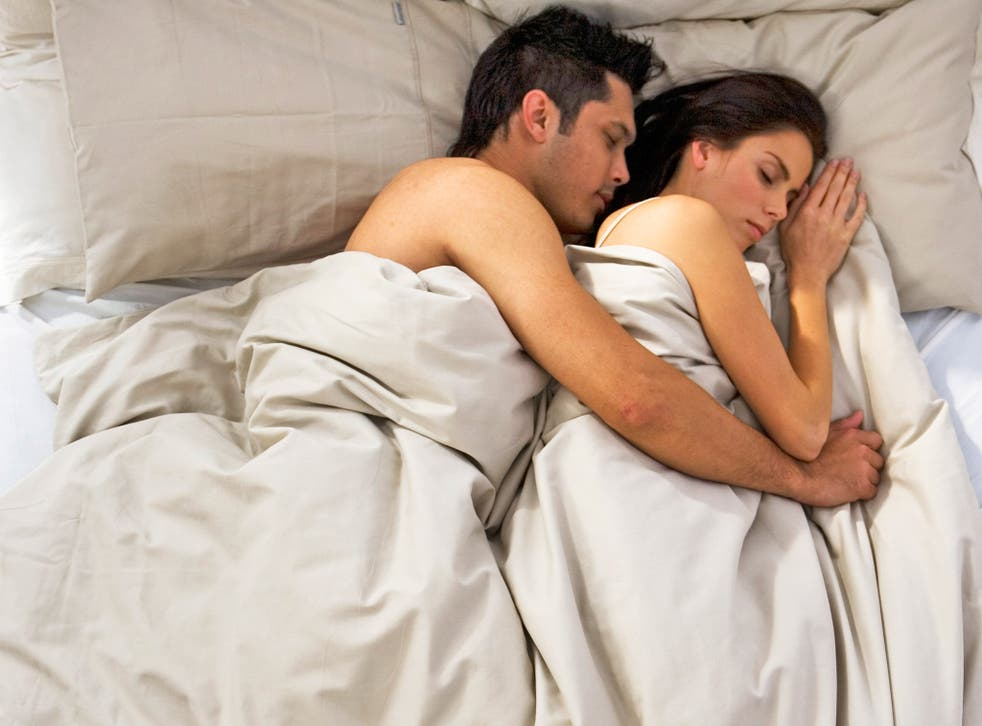 Spooning couple asleep in bed