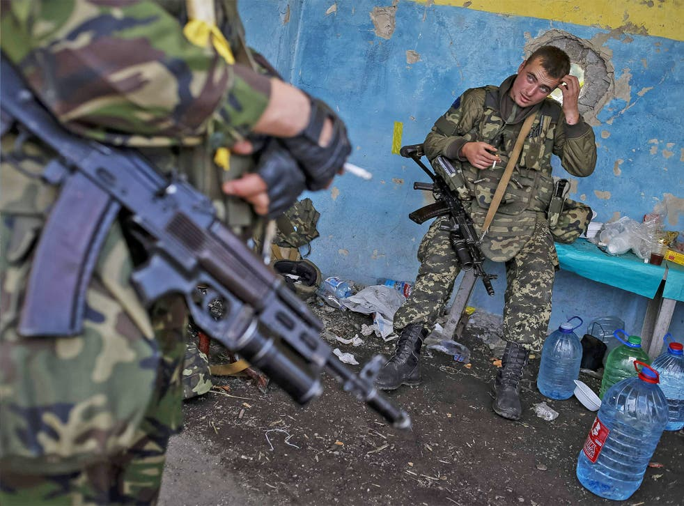 Members of the Ukrainian national guard stand at a checkpoint nearby the town of Slavyanoserbsk, in Luhansk region