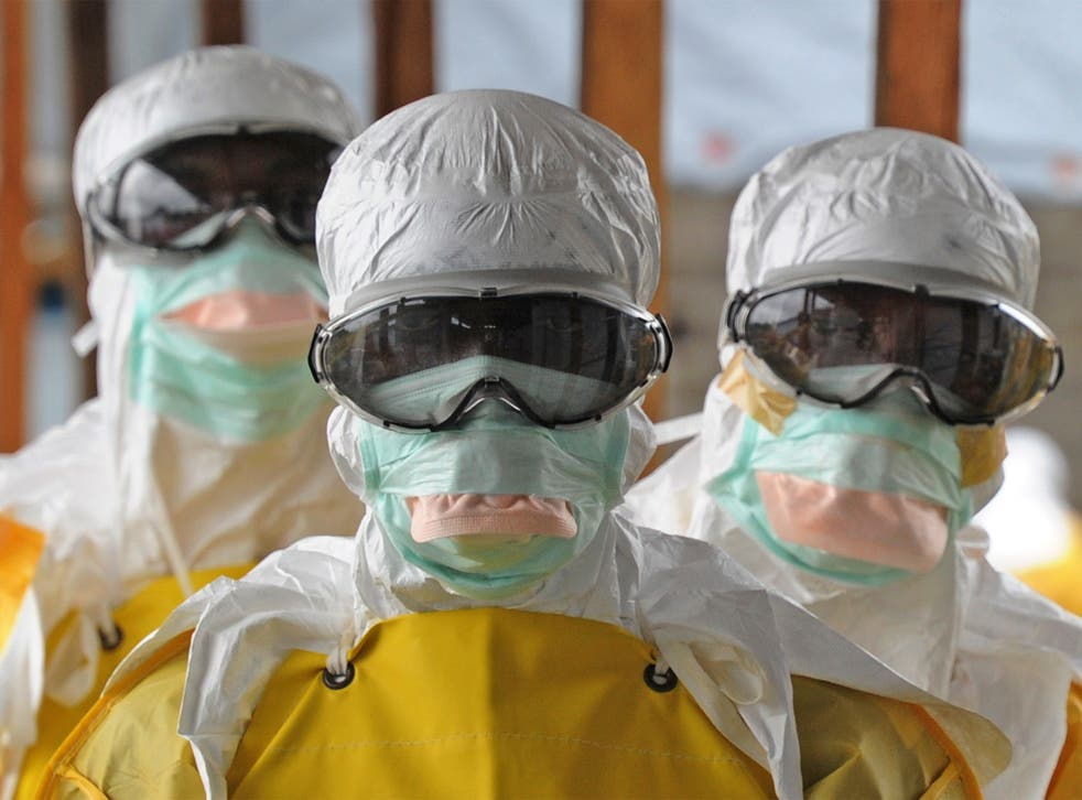 Healthcare workers in Liberia, where the disease has spread, dressed in protective clothing.