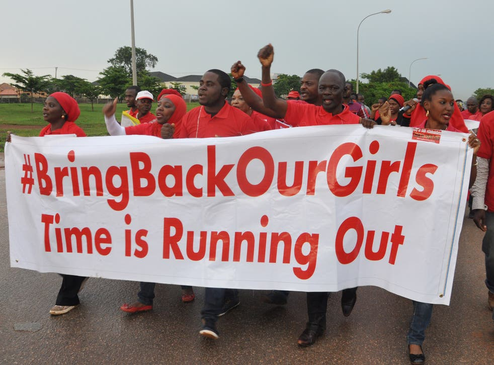 People shout slogans and hold a banner during a demonstration in Abuja, Nigeria. The girls kidnapped by Boko Haram are still missing