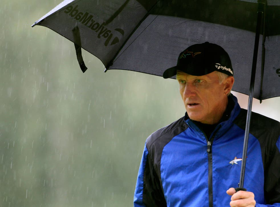 Greg Norman of Australia walks under an umbrella on the 15th green during the second round of the European Masters golf tournament in the Swiss mountain resort of Crans-Montana in August 2012