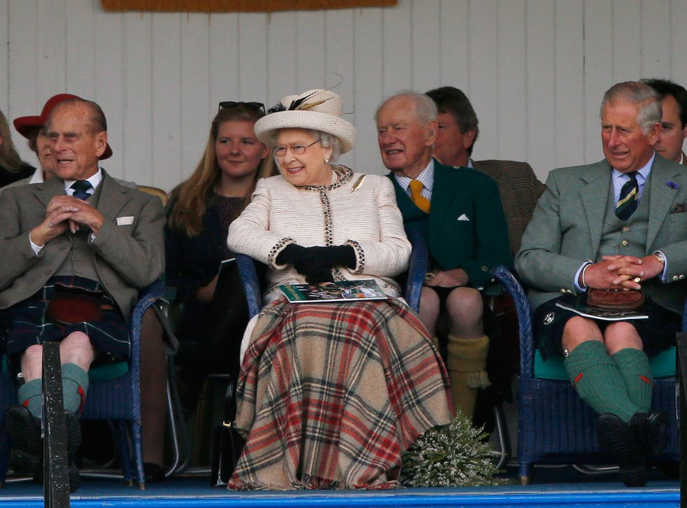 The Queen watches the caber being tossed at the annual Braemar Highland Gathering in Braemar, Scotland, with Prince Philip and Prince Charles, earlier in September