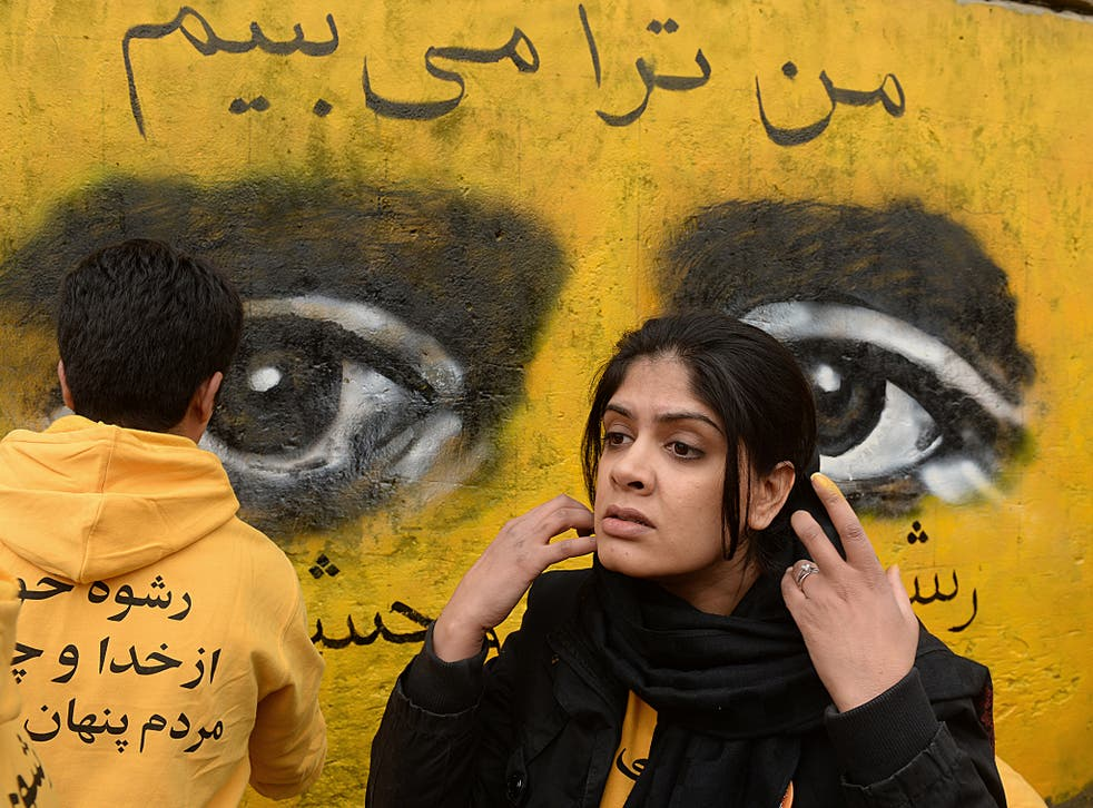 Shamsia Hassani (26) works on a street mural during an event to mark International Women's Day in Kabul