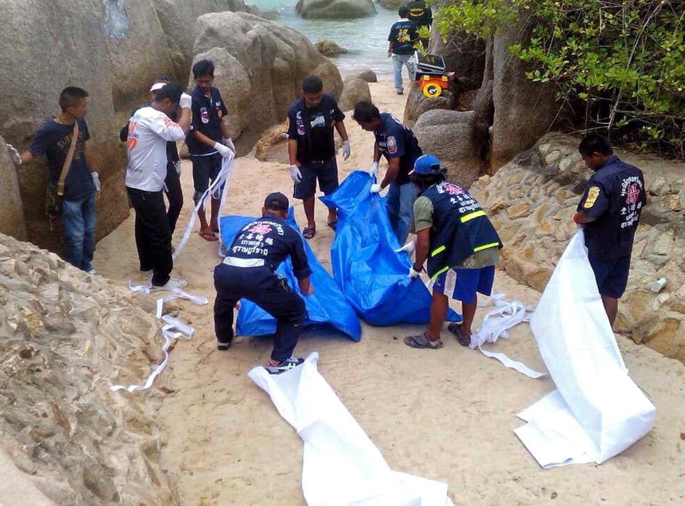 Thai workers carry the bodies of two British tourists on Koh Tao island in the Surat Thani province of southern Thailand