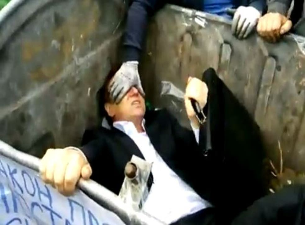 Vitaliy Zhuravskiy was thrown into a dustbin by activists outside the Ukrainian parliament building in Kiev