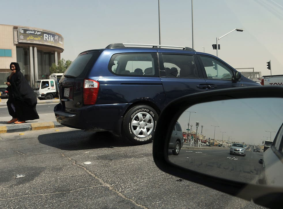 A Saudi woman, unrelated to the incident, walks past stopping vehicles