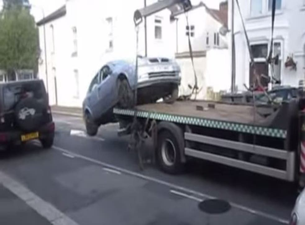 A male driver reverses his Vauxhall Astra from a tow truck