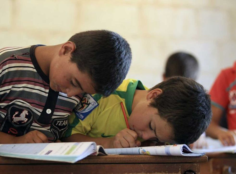 Children attend a class during the first day of school in Idlib countryside earlier this month