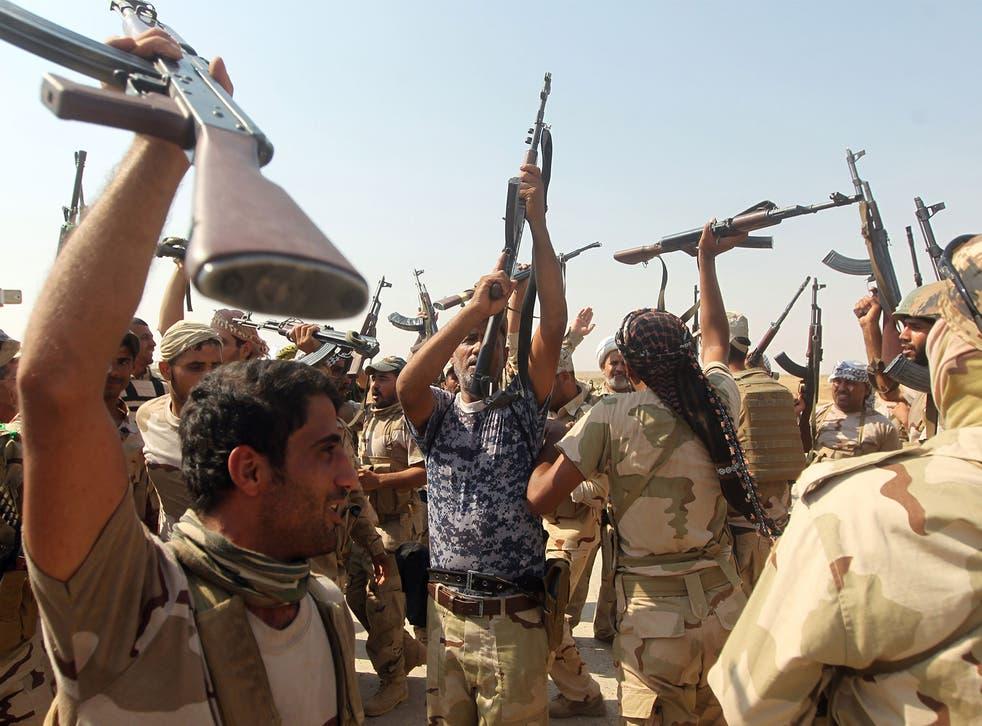 Iraqi volunteer fighters celebrate the breaking of the jihadist siege on the Shiite town of Amerli on September 1, 2014