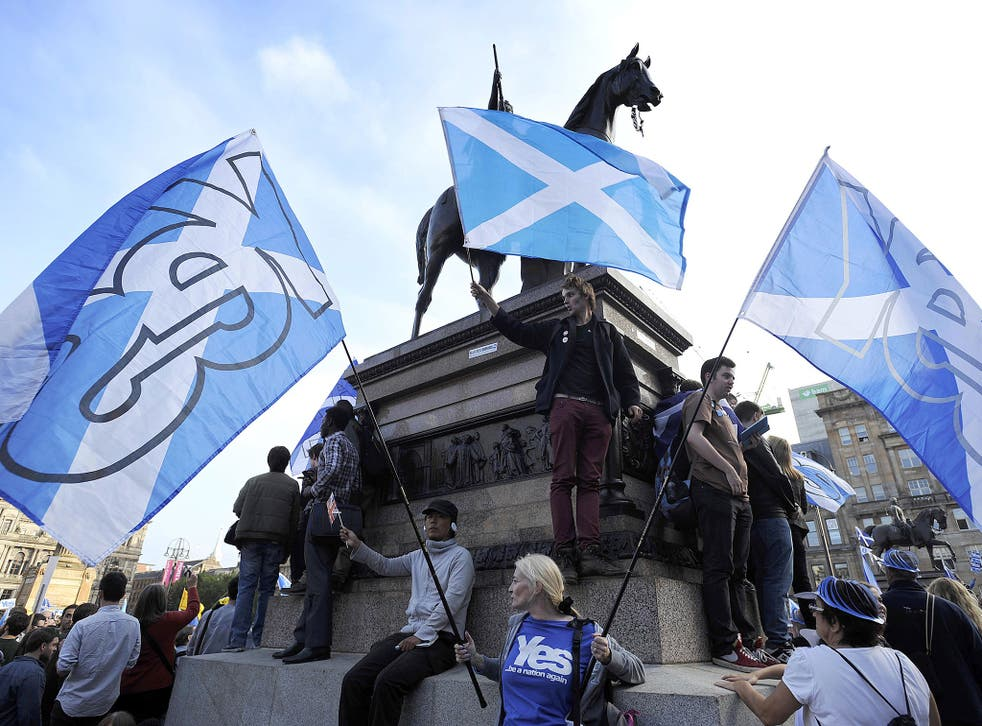 Pro-independence supporters wave Scottish flags in Glasgow's George Square, in Scotland, on September 17, 2014.