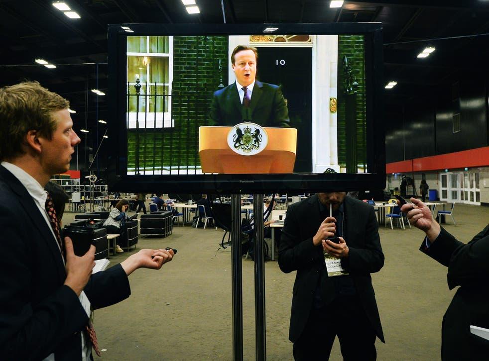 Members of the media listen to British Prime Minister David Cameron's speech on the Scottish referendum