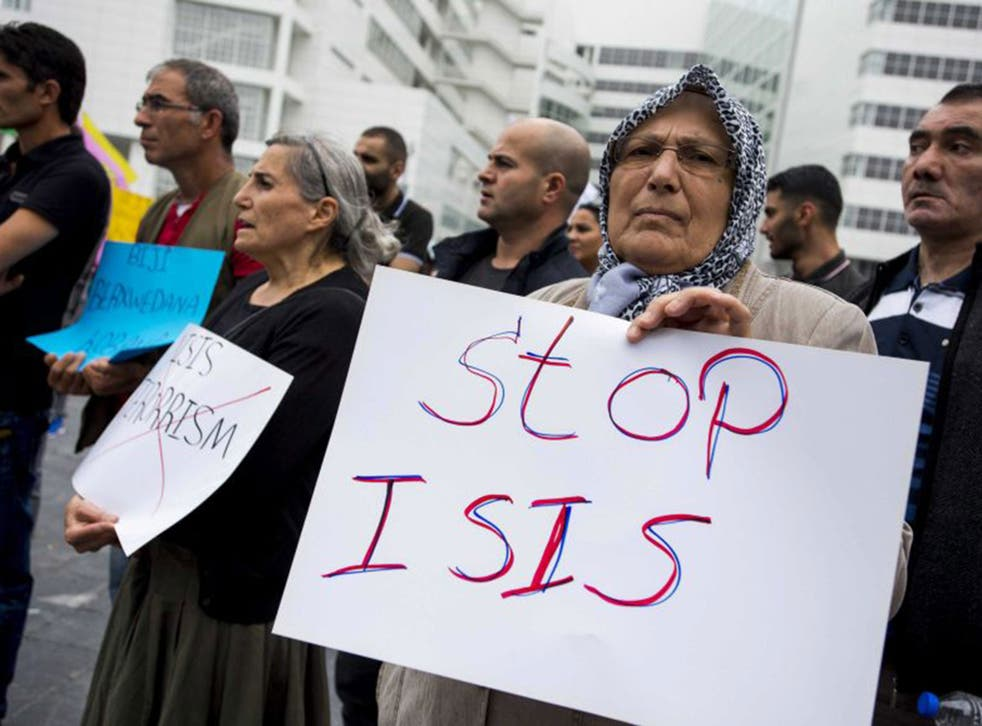 A supporter of the Kurdistan Workers' Association holds a placard during a demonstration against Islamic State (IS) in front  The Hague