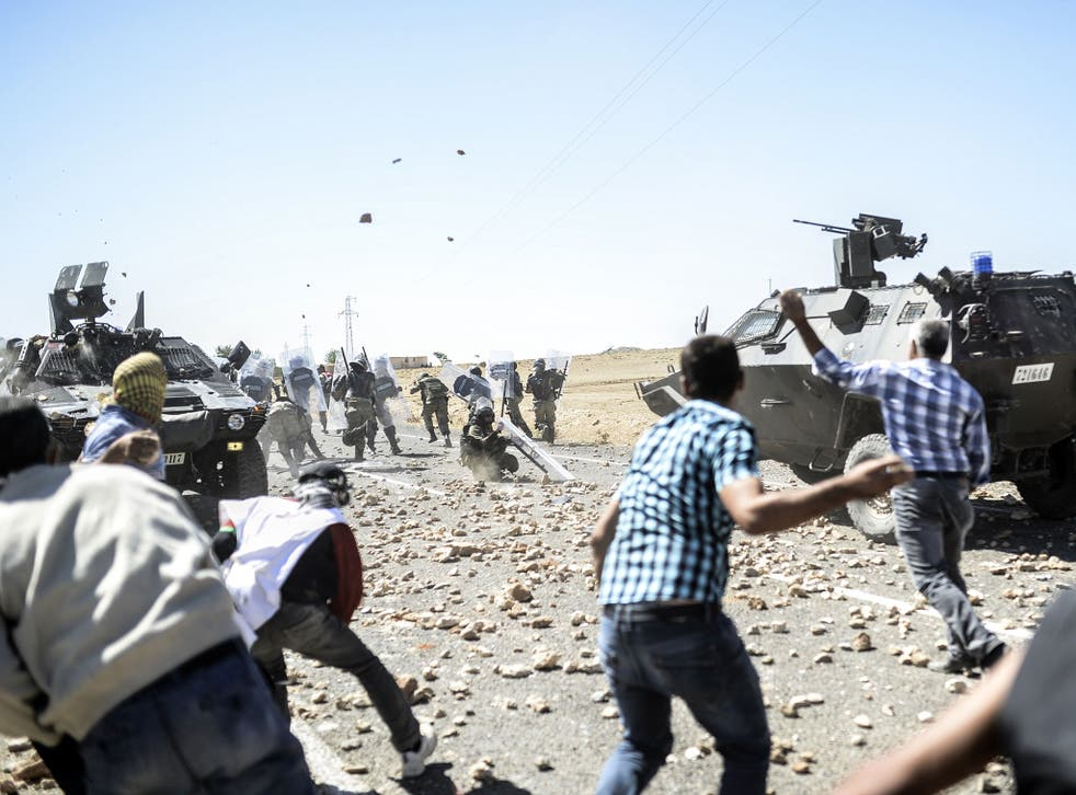 Kurdish refugees clash with Turkish soldiers near the Syrian border after Ankara temporarily closed the Suruc crossing