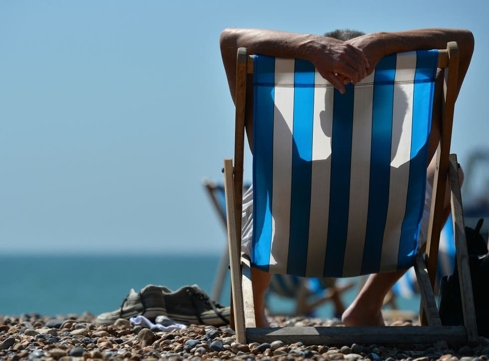 A man relaxes on a deckchair on the beach in Brighton, on the south coast during hot weather