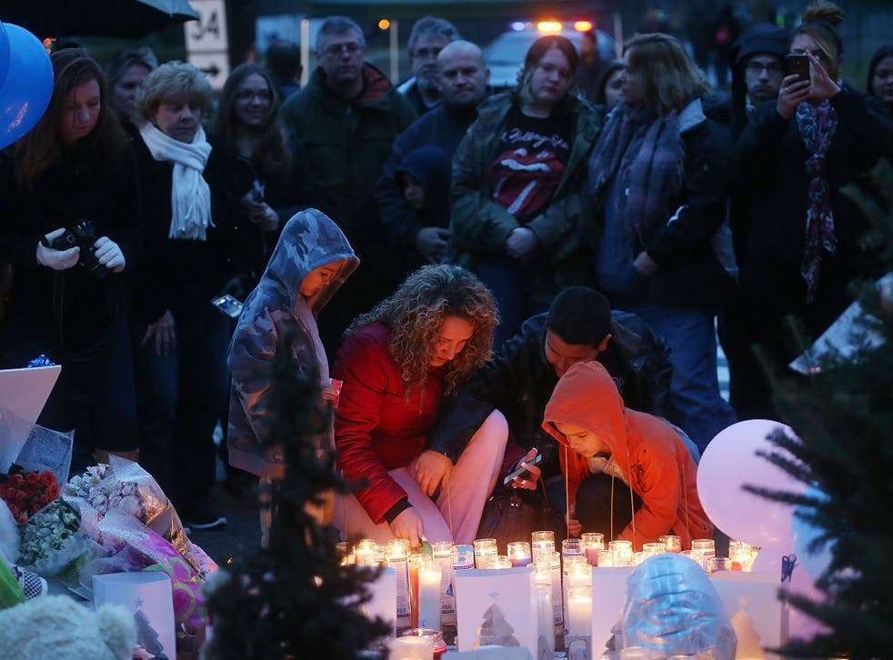 People gather at a memorial for victims following the mass shooting at Sandy Hook Elementary School in Newtown in December 2012
