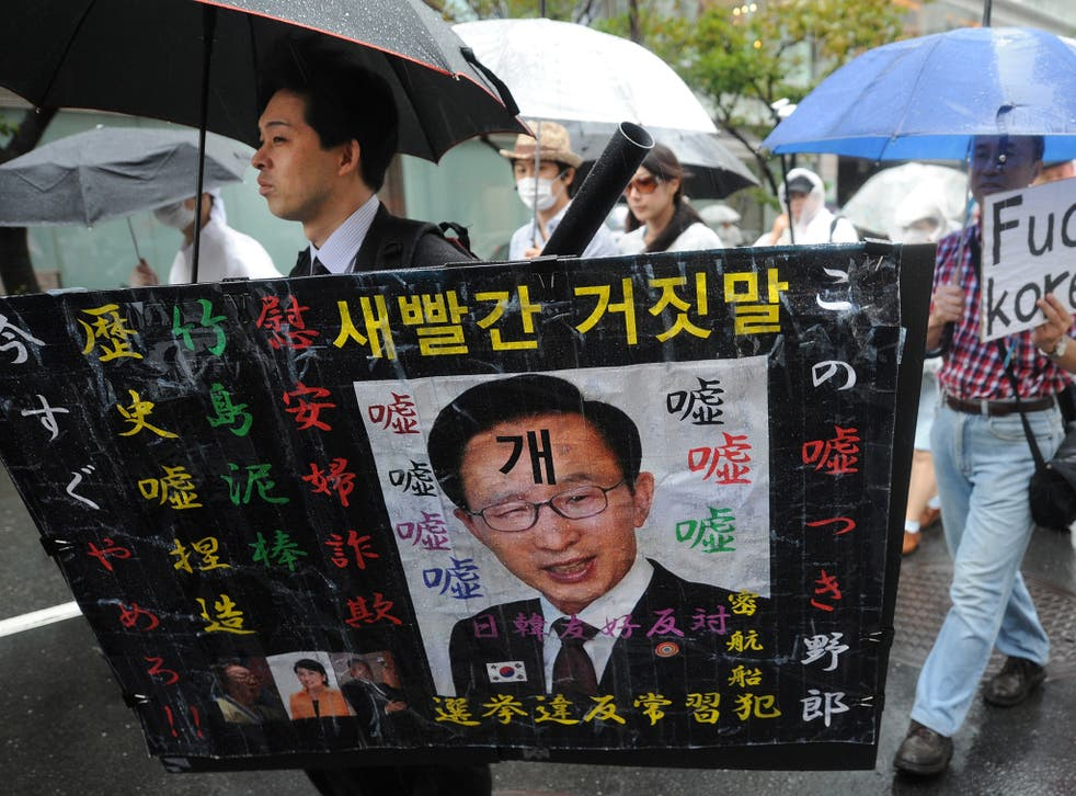 Zaitokukai members wave racist placards during an anti-Korean rally in Tokyo