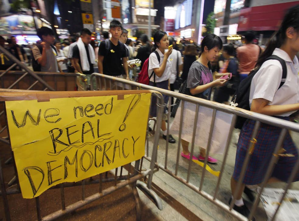 Students gather to attend a sit-in to block main roads of a popular fashion district in Hong Kong