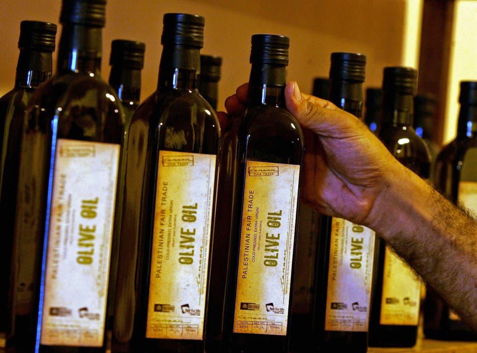 A man grabs an olive oil bottle.