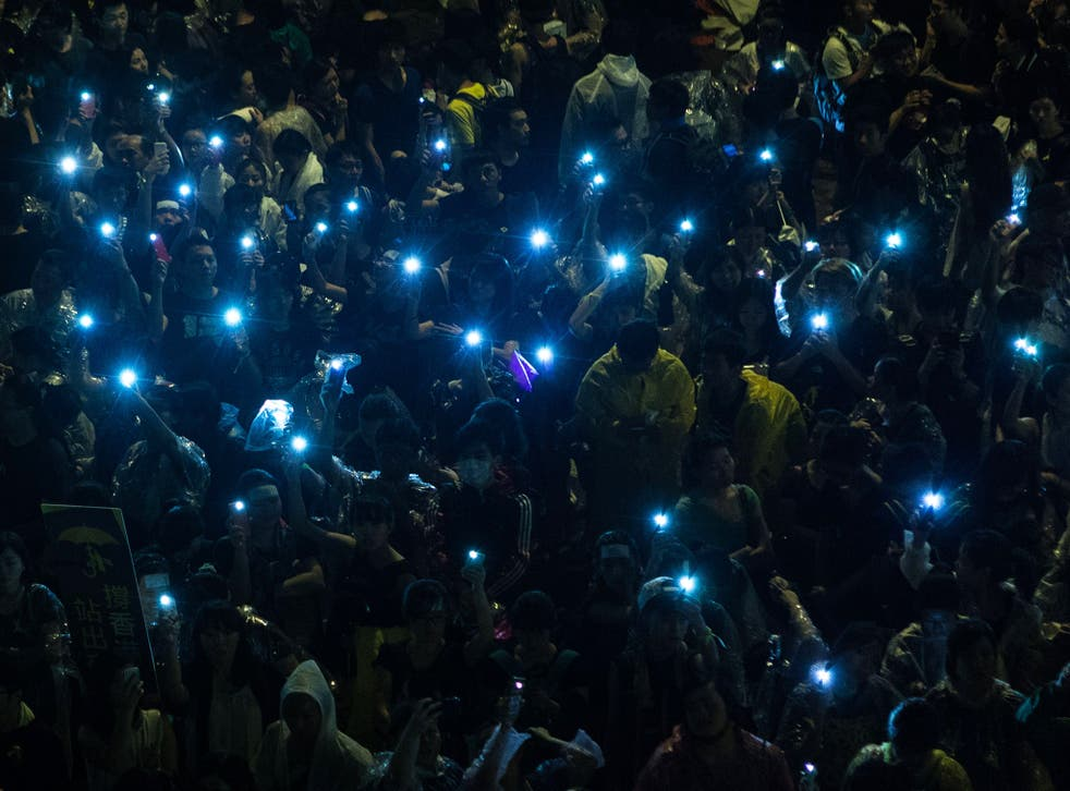 Pro-democracy protesters hold up their mobile phones after heavy rain in Hong Kong. Hong Kong has been plunged into the worst political crisis since its 1997 handover as pro-democracy activists take over the streets following China's refusal to grant citi