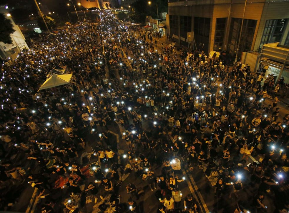 Tens of thousands of pro-democracy demonstrators, some waving lights from mobile phones, fill the streets in the main finical district of Hong Kong, on Wednesday