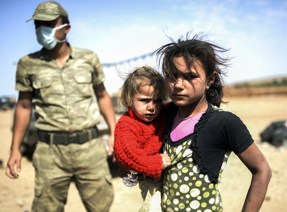 A Syrian Kurdish girl holds her sister in the southeastern town of Suruc in the Sanliurfa province after they crossed the border between Syria and Turkey