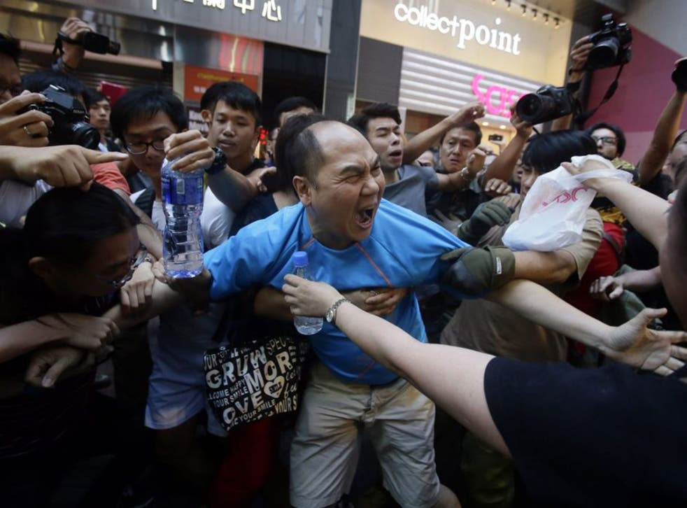 Demonstrators pull at a man protesting against their occupation of the Hong Kong streets on Saturday