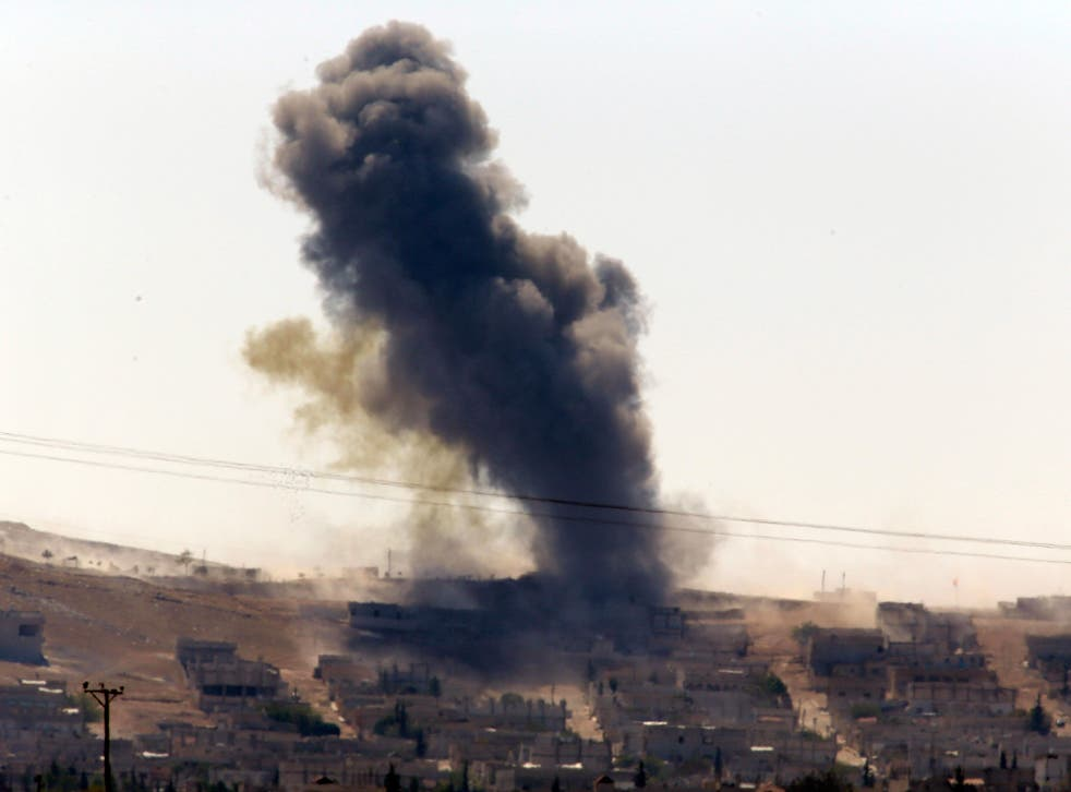 Smoke rises after a shell lands in Kobani in Syria as fighting intensifies between Syrian Kurds and Isis militants