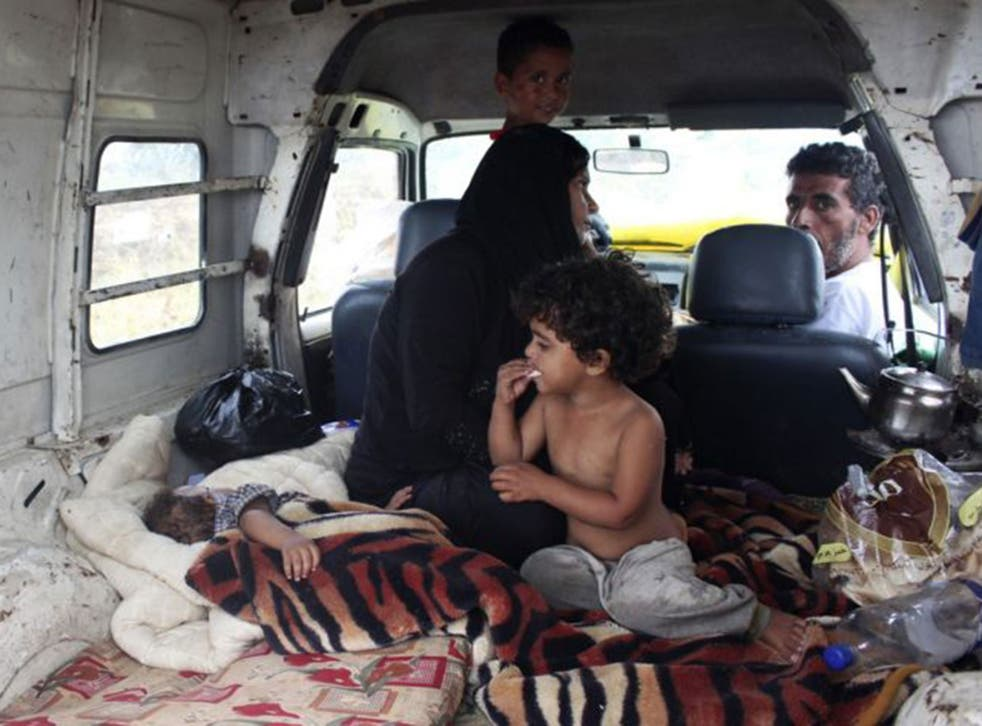 Syrian refugees take shelter inside a van after their makeshift tent was damaged by heavy rain in Halba, northern Lebanon