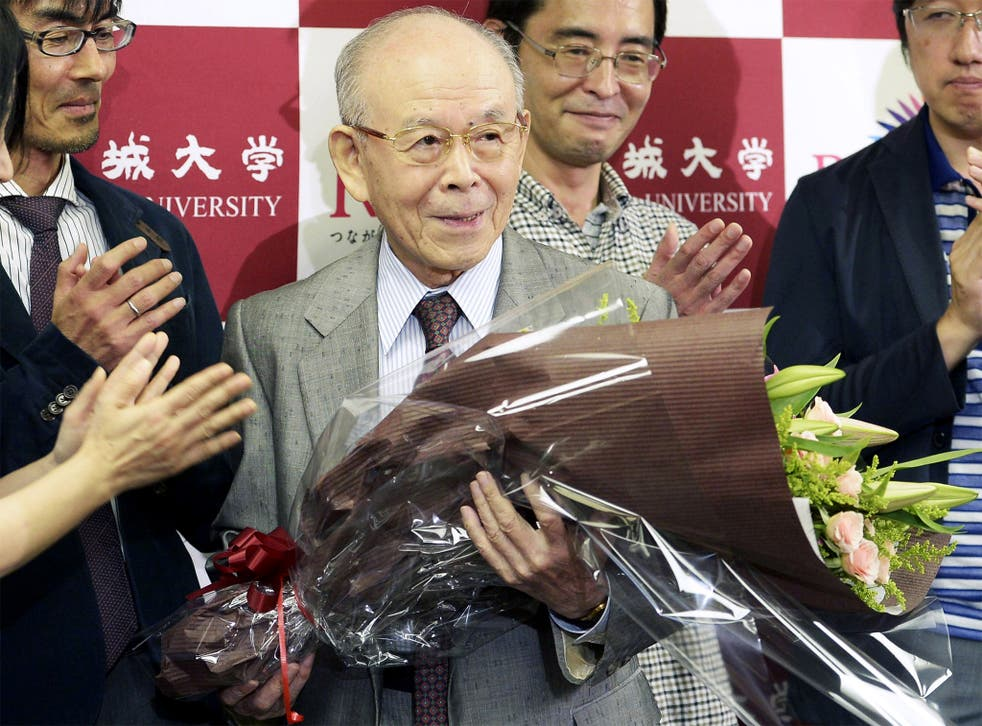 Meijo University Prof. Isamu Akasaki, holds a flower bouquet at a news conference after winning the Nobel Prize in physics at the university in Nagoya, Japan