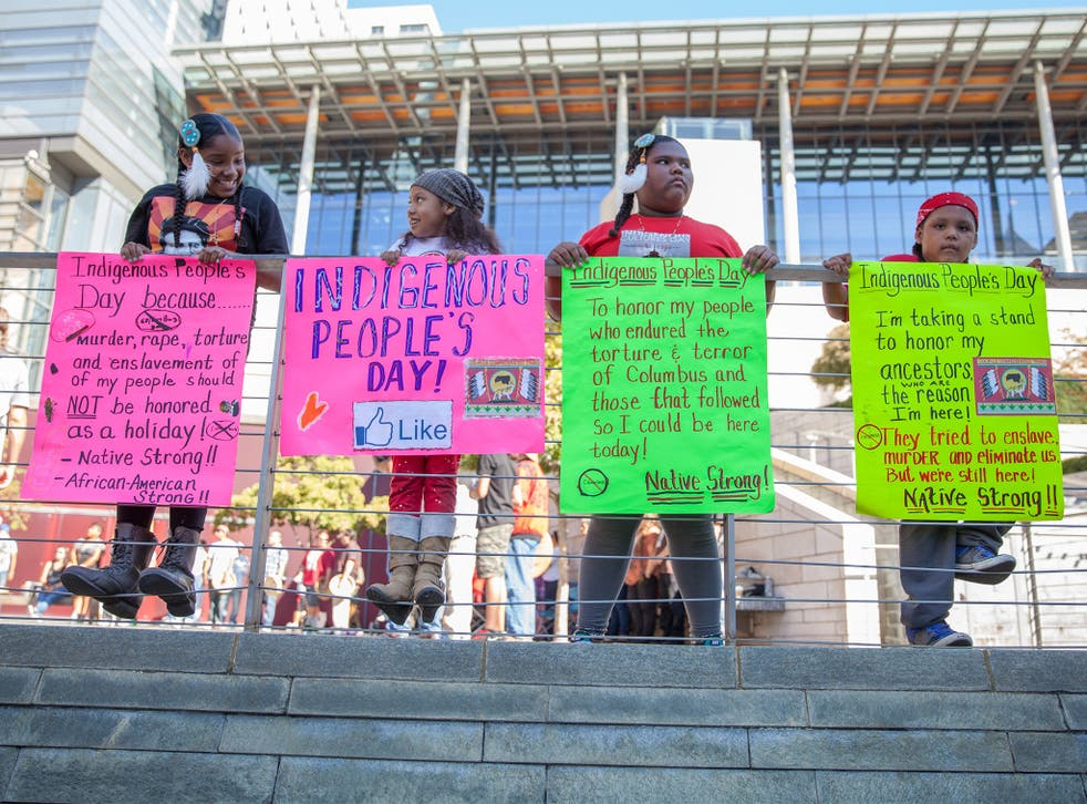 Children hold signs in front of Seattle's City Hall before the city council's historic vote to rename Columbus Day as Indigenous People's Day
