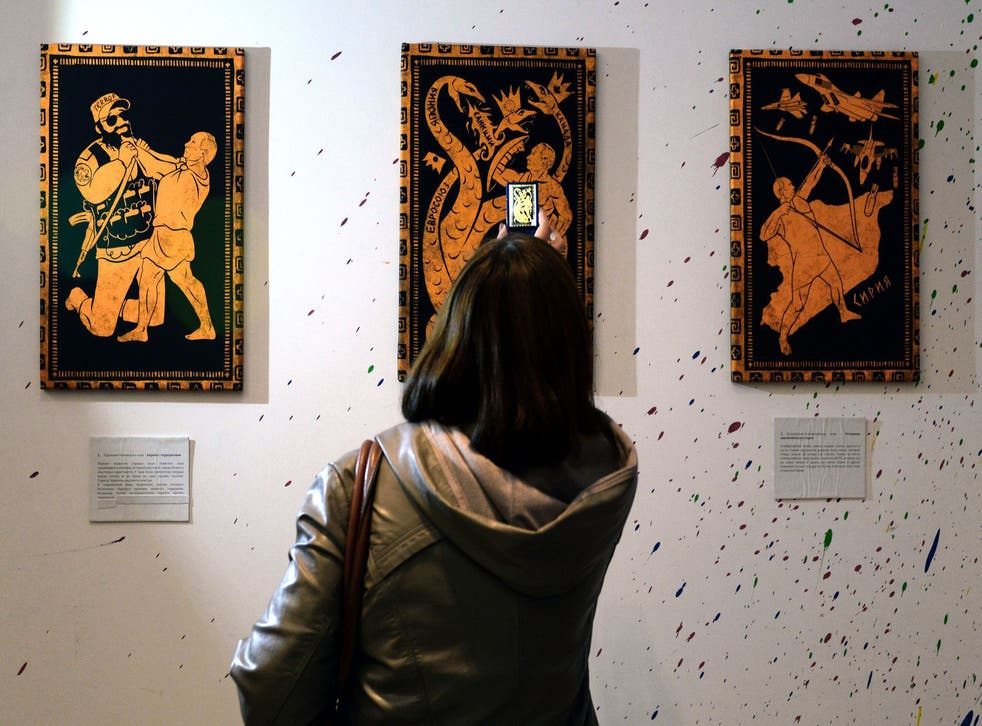 People visit the '12 Labours of Putin' art exhibition marking the 62th birthday of Russia's President Vladimir Putin