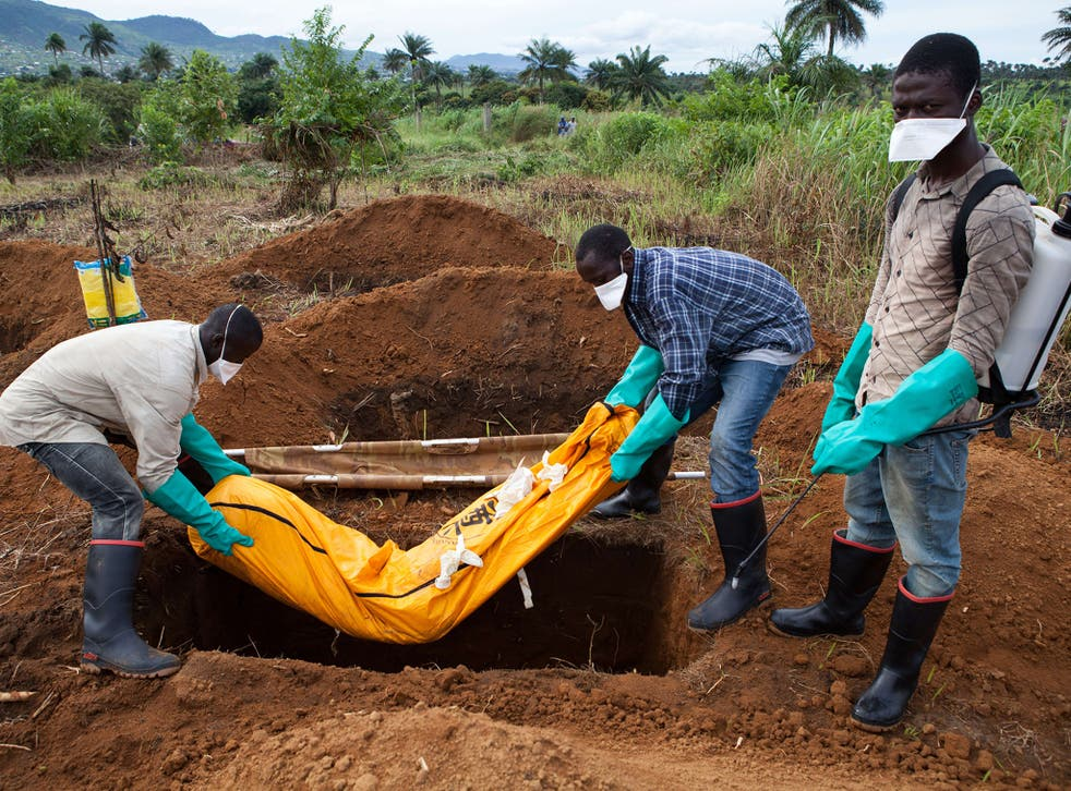 Volunteers in protective suit bury the body of a person who died from Ebola in Waterloo, some 30 kilometers southeast of Freetown