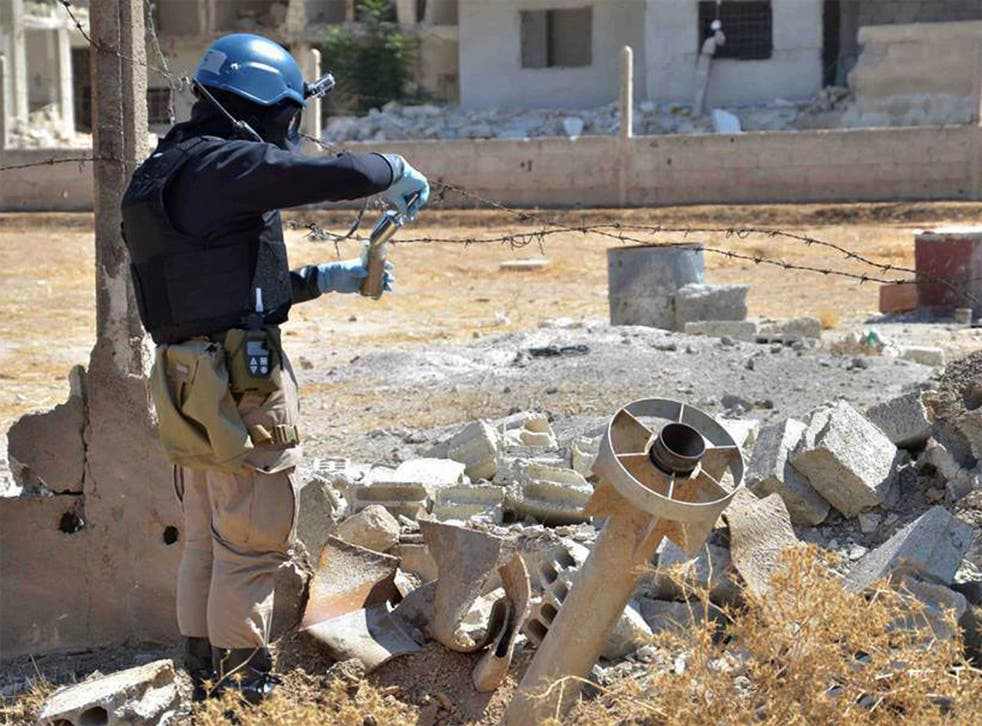 A UN investigator takes samples around a missile found near Damascus suspected of being a chemical rocket