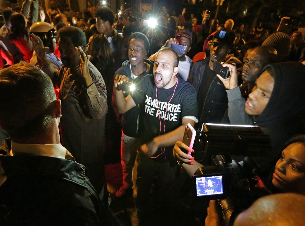 Crowds confront police near the scene in in south St. Louis where a man was fatally shot by an off-duty St. Louis police officer on Wednesday, Oct. 8, 2014