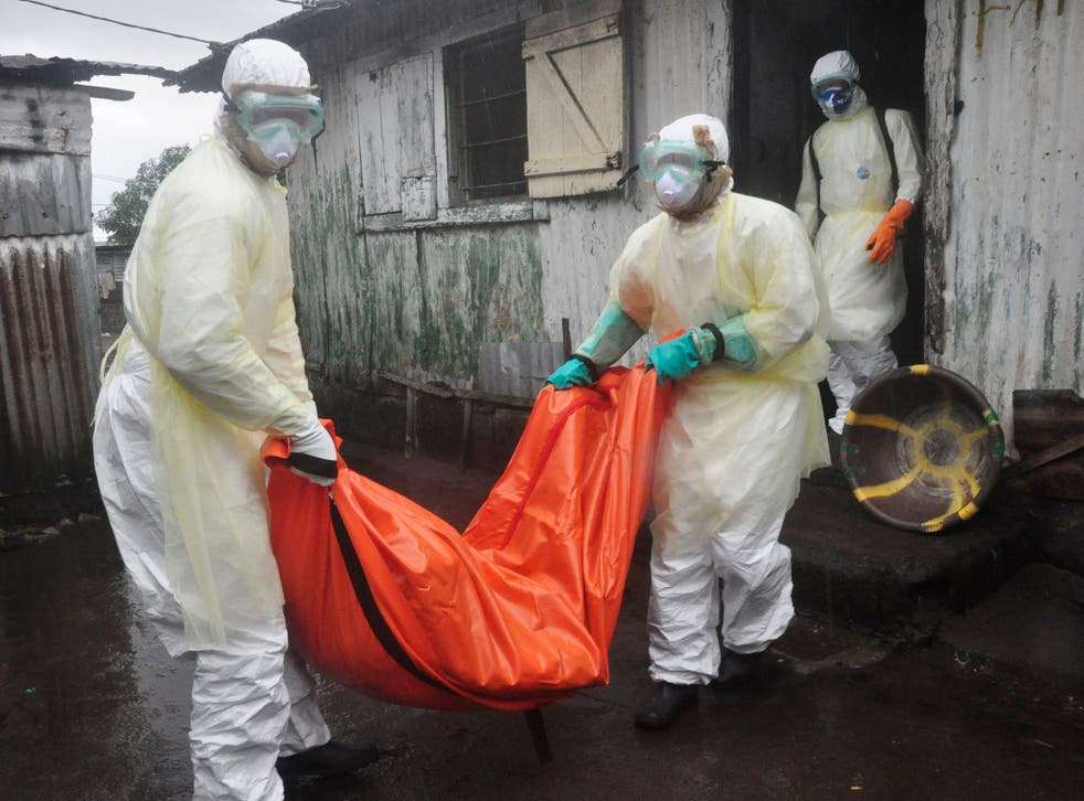 Health workers in protective gear carry the body of a woman suspected to have died from Ebola virus, from a house in New Kru Town at the outskirt of  Monrovia, Liberia