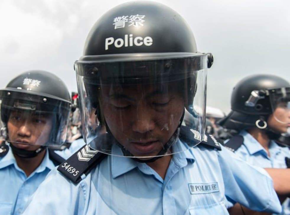 Police form a line to make way for an ambulance as pro-democracy protestors shout slogans outside the government headquarters in Hong Kong on October 3