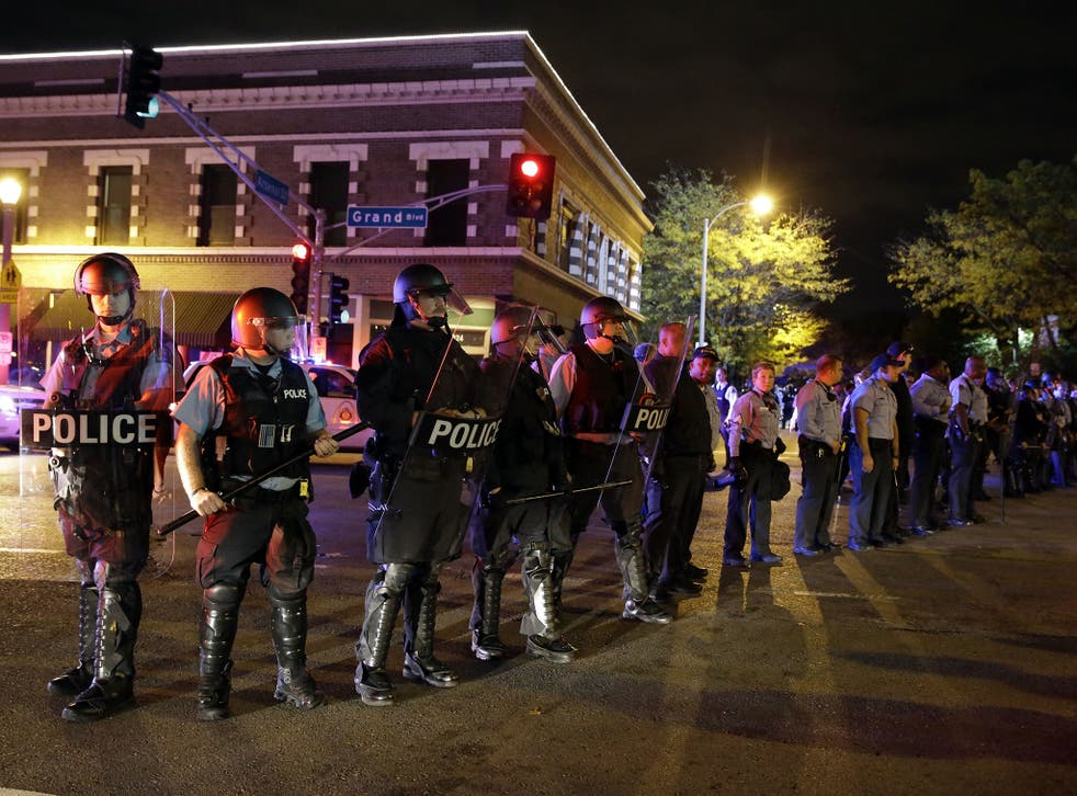 Police wearing riot gear form a line to contain protesters, a day after Vonderrit D. Myers was shot and killed by white, off-duty police officer in St. Louis
